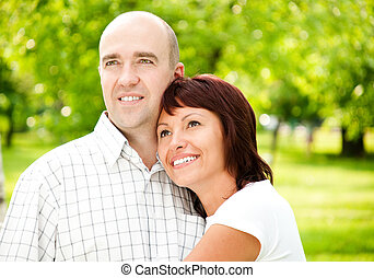 adult couple of husband and wife in park, both smiling and...