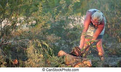 Woman cutting a log into sections with chainsaw - Woman...