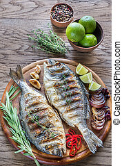 Grilled Dorade Royale Fish on the wooden board - Grilled...