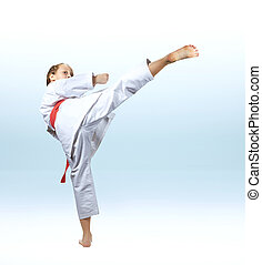 Girl beats a high kick leg on the light background