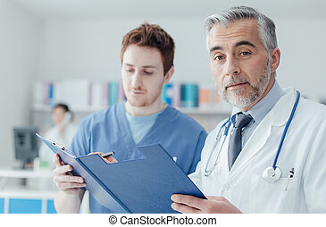 Doctors examining patient's medical records - Doctor and...