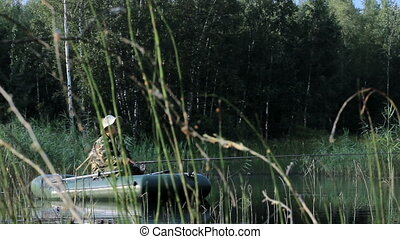 The fisherman floats on the river in an inflatable boat. Early morning with fog on the water. Activities in the wild