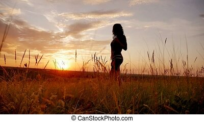 girl puts her hands on sunset woman in the beautiful landscape slow motion video