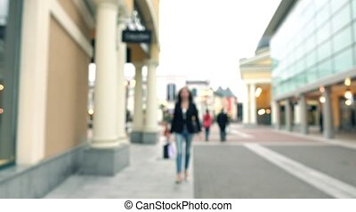 Blurred brunette girl in high heels walking with shopping...
