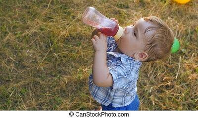 portrait of little boy drinking juice from a bottle in slow motion
