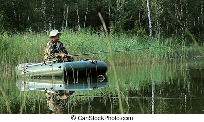 The fisherman floats on the river in an inflatable boat. Moving camera by slider. Activities in the wild