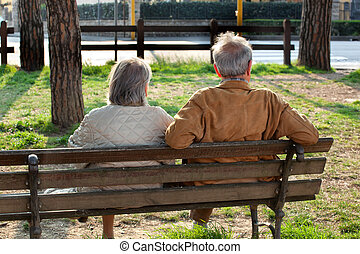 Elderly couple sitting on the bench from behind in a sunny...