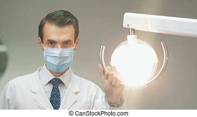 Dentist holding dental lamp - Portrait of a male dentist in...