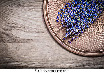 Bundle of dry scented lavender copper tray on wooden board...