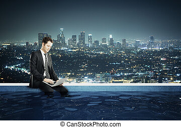 Businessman with computer in rooftop pool - Young...