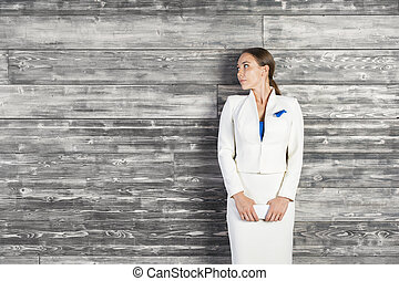 Businesswoman against wooden wall - Thoughtful business...