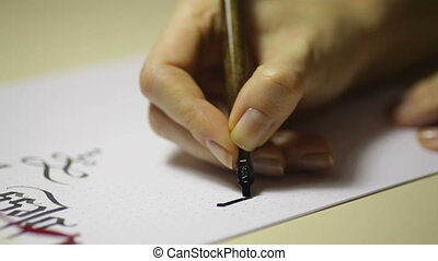 female hand writes a pen calligraphic signs close up