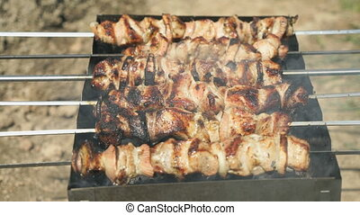 Cooking of pig meat on the metal skewers on coals outdoors