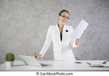Woman with business report in hand standing at white office...