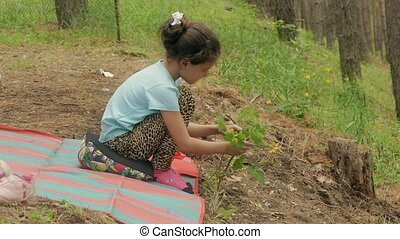 girl sitting hands and touches the grass slow motion video