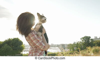 Woman holding dog in hands with backlight sunset