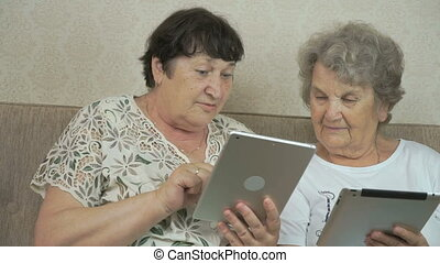 Two elderly sisters holding silver digital tablets