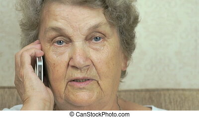 Elderly grandmother talking on the mobile phone indoors