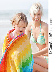 An interested girl and her mother at the beach - An...