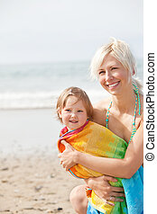 A cheerful girl and her smiling mother at the beach