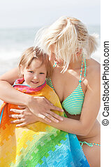 A portrait of a smiling girl in a towel sitting in front of her handsome mother at the beach