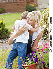 Shy girl embrace her mother in the garden
