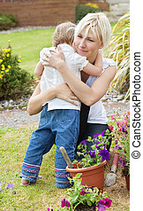 Little girl embrace her mother in the garden