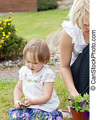Sweet girl with garden tool sitting besides her mother in...