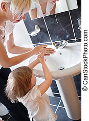 Mother and cute child washing their hands in the bathroom