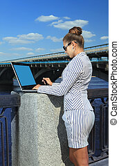 woman with laptop on quay