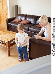 Laughing family in the living room child holding a remote