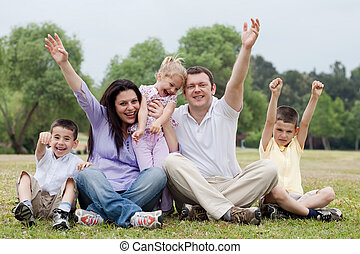 Happy family of five having fun by raising hands on the...