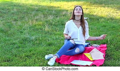 feminine working outdoors in the park - girl lying on the...