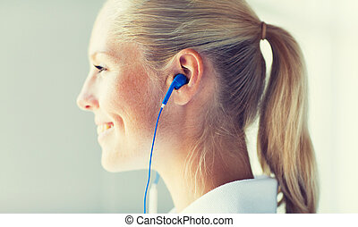 close up of happy woman in earphones at home