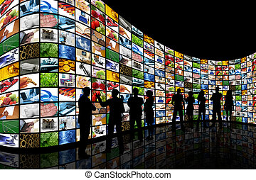 People looking at wall of screens - People silhouettes stood...