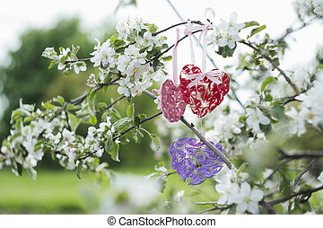 Colorful heart made of quilling on apple blossom branch