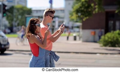 happy teenage couple with smartphones in city - summer...