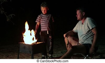 Family have a rest in camp at night near campfire