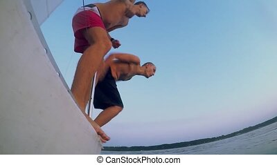 Young friends jumping into sea from the sail yacht - Group...