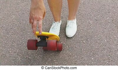 teenage girl putting short modern skateboard down -...