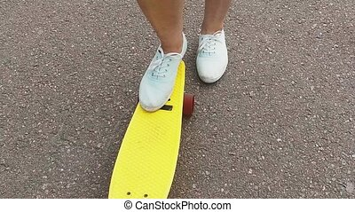 teenage girl picking short modern skateboard up -...