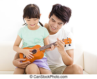 happy Father Teaching daughter To Play ukulele