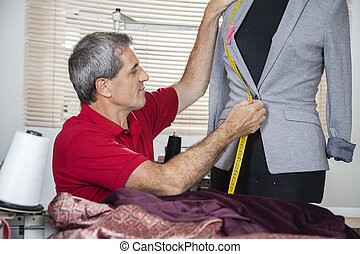 Fashion Designer Measuring Suit On Mannequin - Mature male...