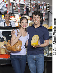 Happy Young Couple Holding Cheese At Grocery Store