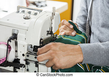 Fashion Designer Sewing Fabric At Workbench - Cropped image...
