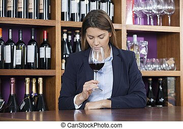 Customer Smelling Red Wine At Counter In Shop - Mid adult...