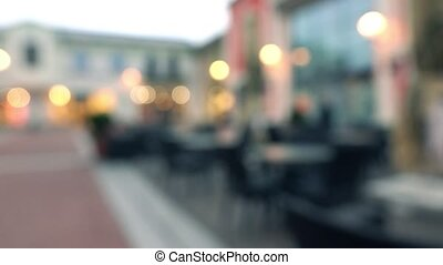 Blurred empty street cafe in the rainy evening. 4K...
