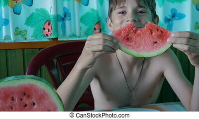 A child eats a slice of watermelon, he is sitting at a table...