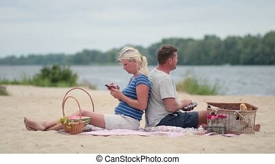 Couple sitting back to back and texting on phone