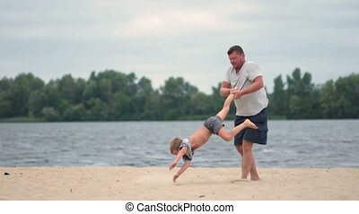 Happy father and son playing on summer beach - Happy excited...